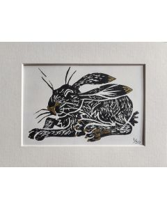 Lino cut limited edition print of a sunbathing hare with gold ink embellishments.